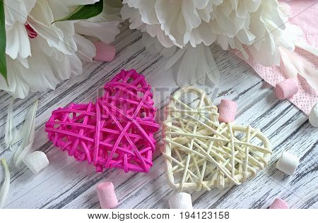 Peonies Flowers Rattan Hearts Marshmallow On A White Wooden Background - Stock Image.