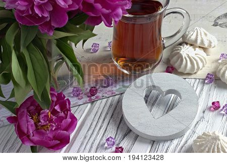 Peonies Flowers Pink Glass Of Tea With White Wooden Heart Marshmallow On A White Wooden Background -