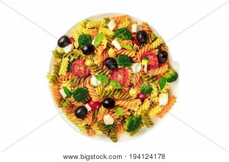 A photo of a plate of pasta salad with basil leaves, shot from above, isolated on a white background
