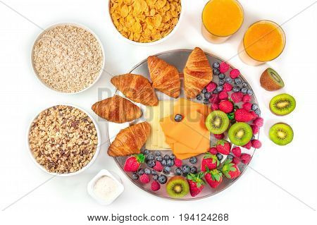 Overhead photo of a continental hotel breakfast on white background. An assortment of croissants, cheese, fresh fruit, orange juice, cereal bowls, yoghurt cups. With a place for text