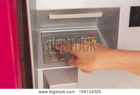 Hand of a woman push button in ATM using an ATM. Woman using an ATM machine.
