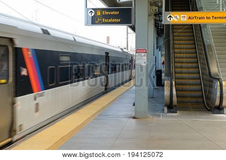 NEWARK, NEW JERSEY, USA - APRIL 25, 2016 - A train in motion arriving at a Newark International Airport train station, New Jersey, USA