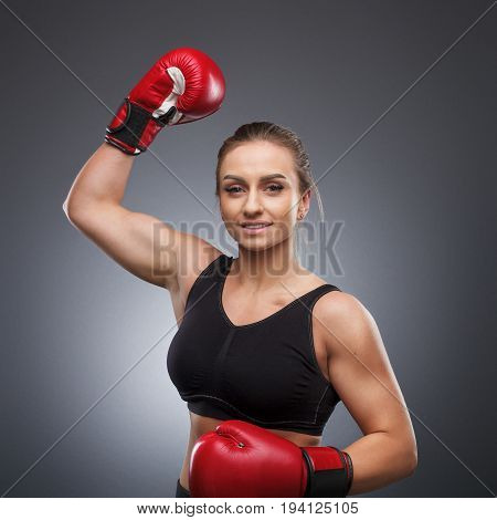 Smiling woman with fit body wearing boxing gloves holding hand in air.