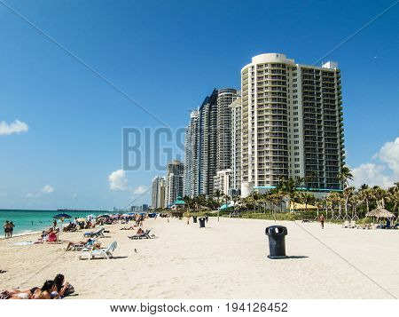 Sunny Isles Beach USA - March 22 2011: Hotel beachfront resorts with people relaxing and sunbathing by water