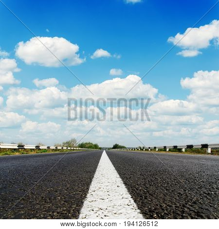 black asphalt road with white line on center and blue sky with clouds over it