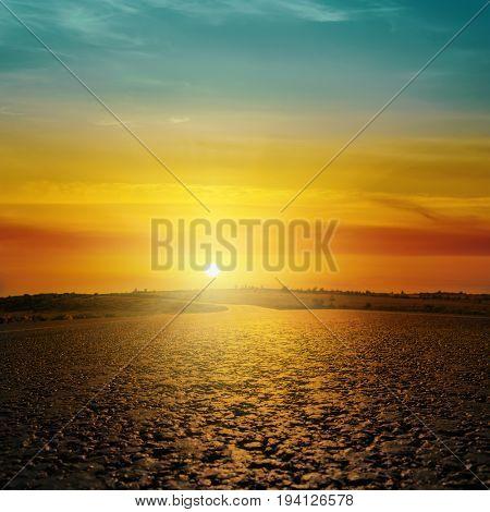 good orange sunset in clouds over asphalt road