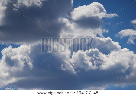 White woolpack clouds on the blue sky