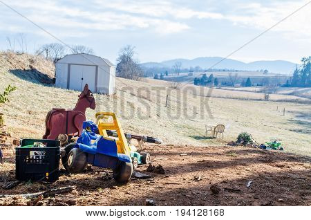 Old childrens toys and tractors on farm by barn in pile in field in Virginia countryside