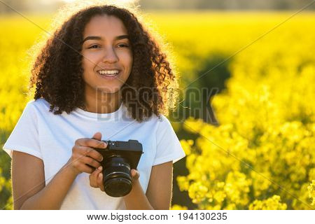 Beautiful happy mixed race African American girl teenager female young woman smiling outdoors in sunshine taking photographs with a camera