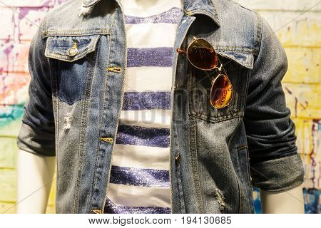 In the shop window a mannequin dressed in a T-shirt a denim jacket in his pocket glasses.