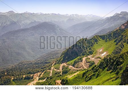 Mountain landscape: steep mountains covered with forests form a deep gorge on the of a mountain winding road with steep turns - a mountain serpentine.