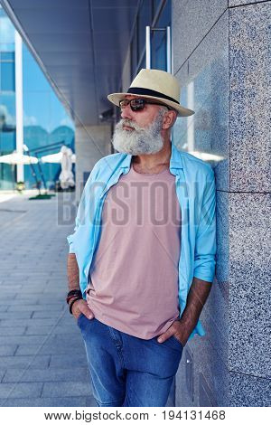 Handsome elderly man wearing sunglasses looking far, spending time outdoors on sunny day, mid shot