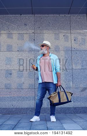 Elderly bearded man standing and smoking e-cigarette holding bag in hand wearing casual clothing, mid shot