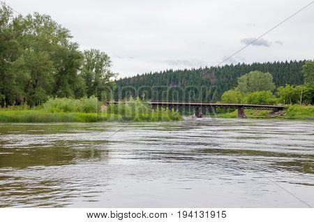 Old Iron Bridge Over The River Ufa With The Broken Icebreaker