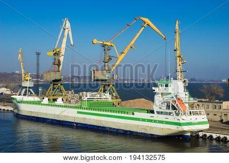 Cargo cranes transship bulk in the dock of Industrial Port