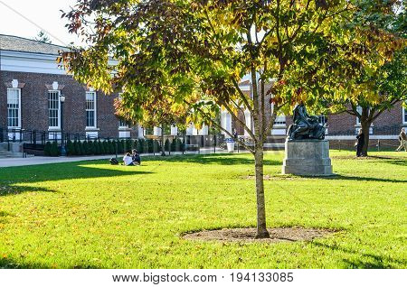 Charlottesville USA - October 20 2013: Autumn on lawn of University of Virginia with Old Cabell Hall Homer statue and students sitting on grass