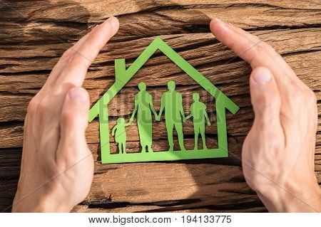 Person Protecting Family Paper Cut Out With Hands On Wooden Desk