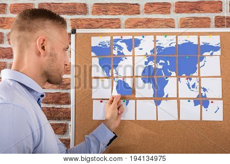 Businessman Looking At World Map Made On Notes Over The Bulletin Board