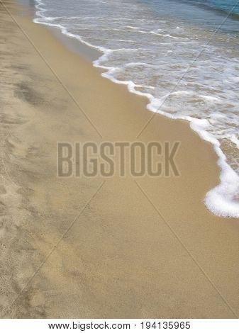 Sandy sea coast with small wave.