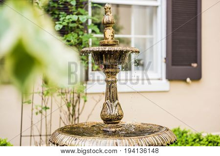 Vintage aged European fountain in Frederick Maryland in downtown during summer with water droplets
