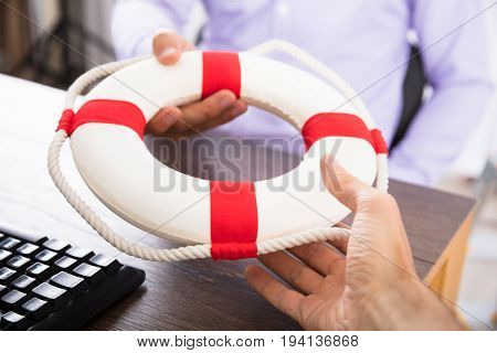Close-up Of A Businessman's Hand Passing A Lifebuoy To His Partner In The Office