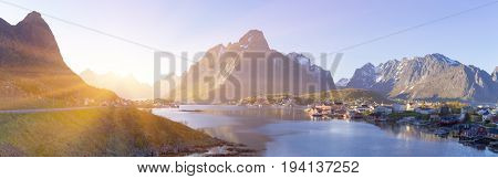 Panorama of Island of Hamnoy, Reine on the Lofoten in northern Norway. The Typical Norwegian fishing village of Reine under midnight sun, blue sky, with the typical rorbu houses.