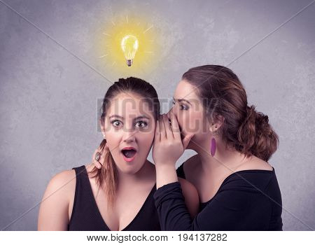 A young girl has an idea illustrated with a drawn glowing light bulb above the head, while a friend whispers a secret in her ear concept.