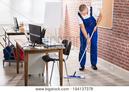Young Male Janitor Mopping Hardwood Floor At Workplace