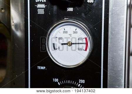 White temperature sensor on an industrial dirty black metal oven in the kitchen of a cafe or restaurant shows a temperature of 450 degrees Celsius