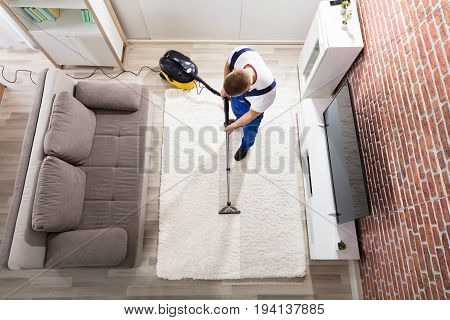 Elevated View Of Male Janitor Cleaning Carpet With Vacuum Cleaner At Home