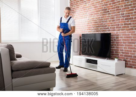 Smiling Male Janitor In Uniform Sweeping Floor With Broom At Home