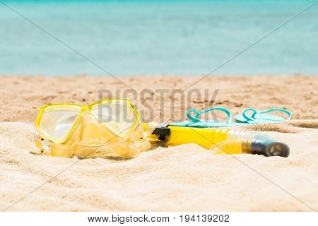 The Yellow Snorkel Mask And Turquoise Slippers On The Sand At Beach