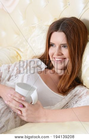 Beautiful young woman lying on soft beige bed with white cup