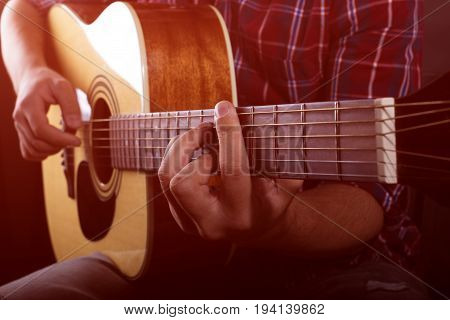 Practicing in playing guitar. Handsome young men playing guitar.