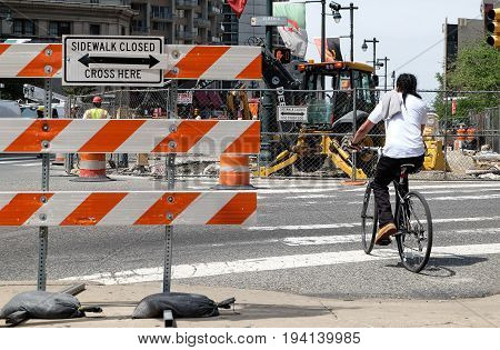 PHILADELPHIA, UNITED STATES - April 25, 2016: Bicycler on a crosswalk near construction area and sign of sidewalk closed.