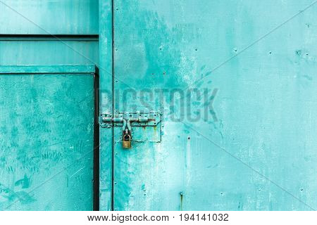 close up on green door with the key locked abstract background with vintage filter. to show the old texture on metallic.