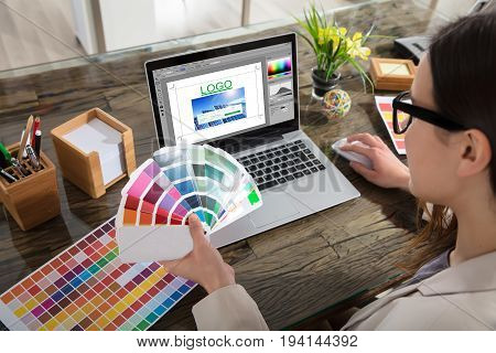 A Woman Holding Color Swatches Using A Laptop With Logo Design Software On The Screen