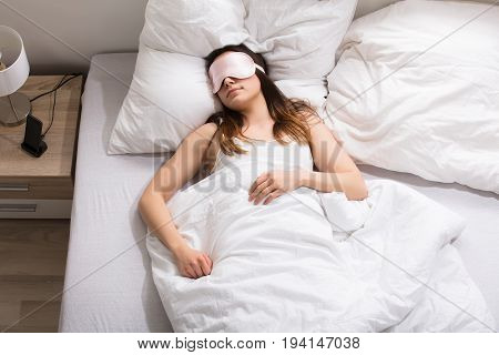 Elevated View Of A Woman With Pink Mask Sleeping On Bed