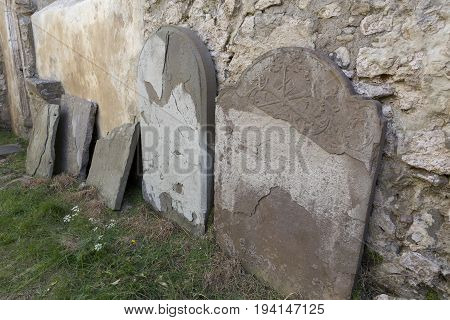 Old broken gravestone laying up against the wall at an old church