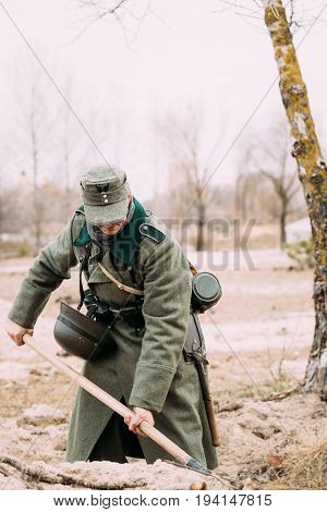 Gomel, Belarus - November 26, 2016: Unidentified Re-enactor Dressed As A German Infantry Soldier Of The World War Ii Digging A Trench In Autumn Forest.