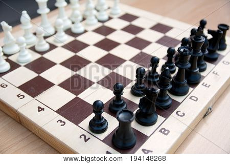 A photo of a chessboard with chess pieces on it from the side of black figures