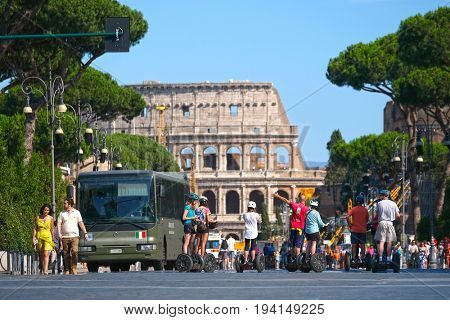 Roma, Italy - July, 2, 2017: group op the tourists on segways stand infront of Colosseum, ancient Roman amphitheater, one of the main sights of Rome