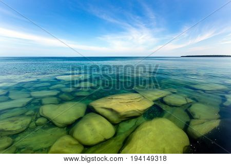 The clear waters of Lake Superior reveal large rocks and stones underwater. This cove with pristine waters is located near Au Train Michigan