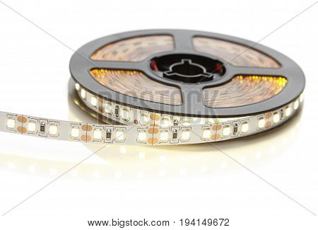 Reel of a diode strip with warm light on a white background