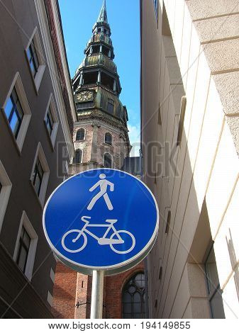 Pedestrian and cycling zone sign with Saint Peter's church on background. Riga, Latvia.