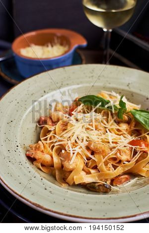 Pasta with seafood and cheese. Glass of white wine. Rustic style.