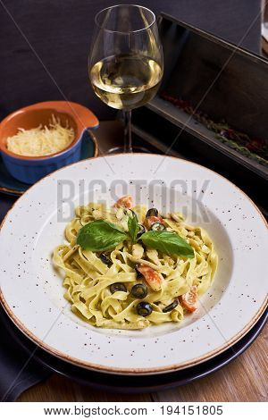 Pasta with chicken, olives and cheese on ceramic plate with glass of white wine. Main course. Restaurant food.