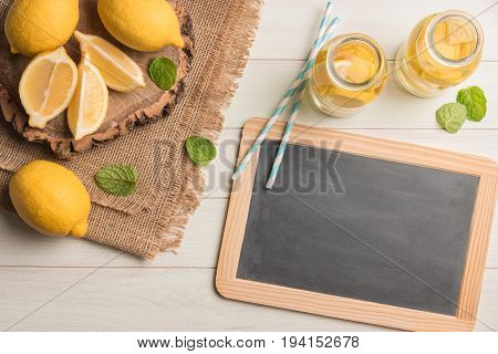 Glass of homemade lemonade with mint and lemon wedges. Top view with copy space.