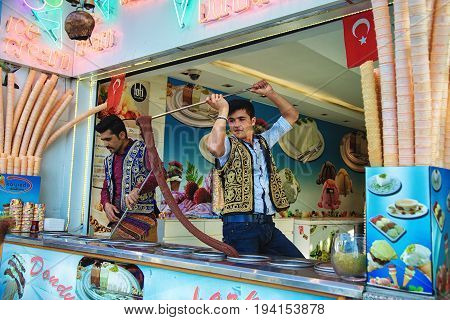 ISTANBUL TURKEY - MAY 2 2017: Young dondurma ice-cream sellers dressed in traditional Turkish costume in the street shop