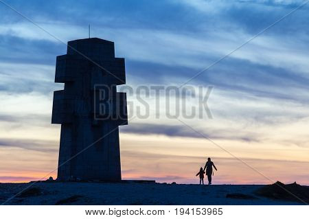Mother and child visiting the Monument to the Bretons of Free France on the cliffs of the Pen-Hir peninsula in Crozon, silhouetted against sunset.